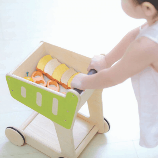 child pushing plantoys shopping cart