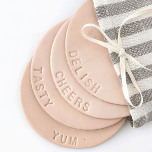 leather coaster set displaying hand-pressed words