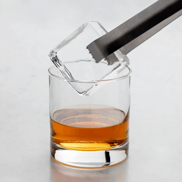 Peak clear ice cube being placed into glass